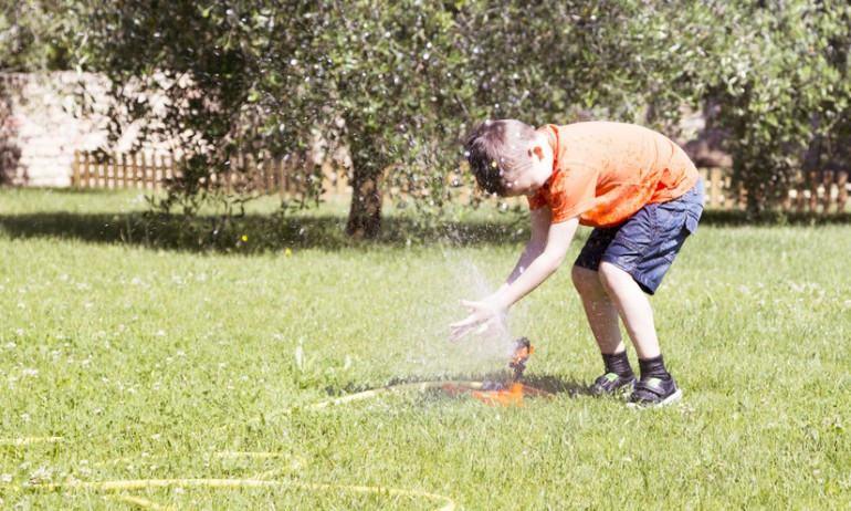 happy-child-playing-with-water-in-the-garden-on-a-sunny-day