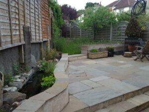 Sandstone Paving with Pond and Scaffolding Raised Bed, Bedminster